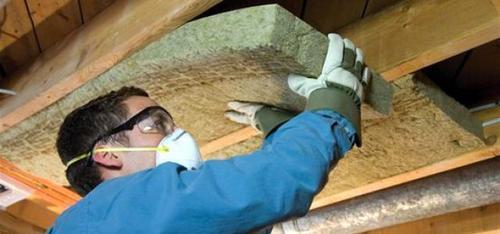 Мастер укладывает минеральную вату