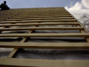 Строитель на крыше дома