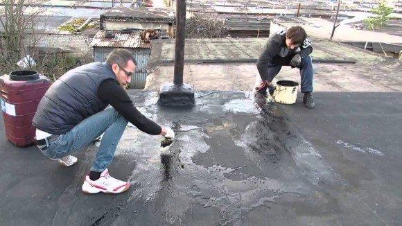 Мужчины работают на крыше гаража
