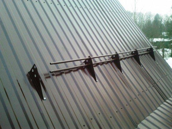 Трубчатый снегозадержатель на крыше из профнастила